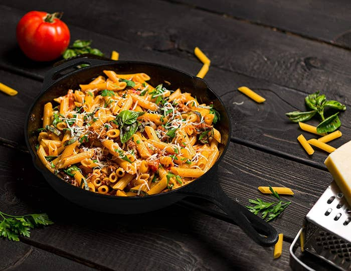 Penne with meat crumbles, tomato, basil, and cheese in a black cast-iron skillet