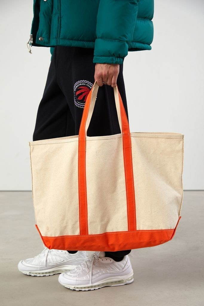 The large beige bag with orange straps and orange bottom