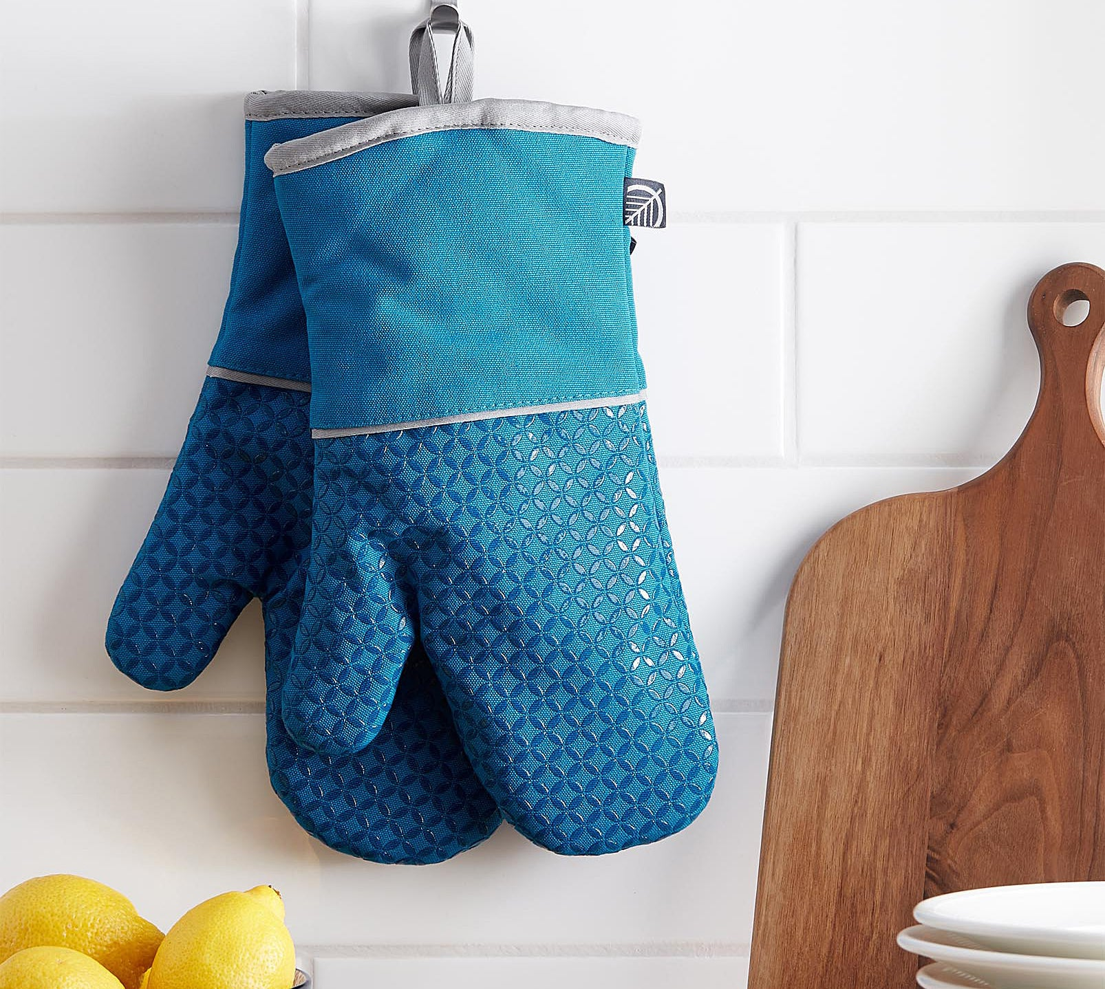 A pair of oven mitts hanging from the wall