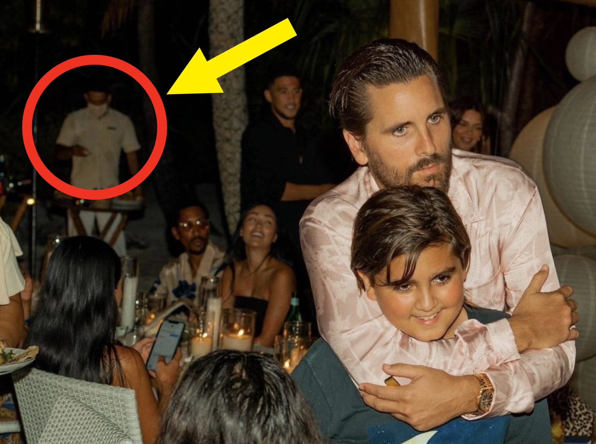 Scott and Mason Disick hugging as a masked waiter works in the background.