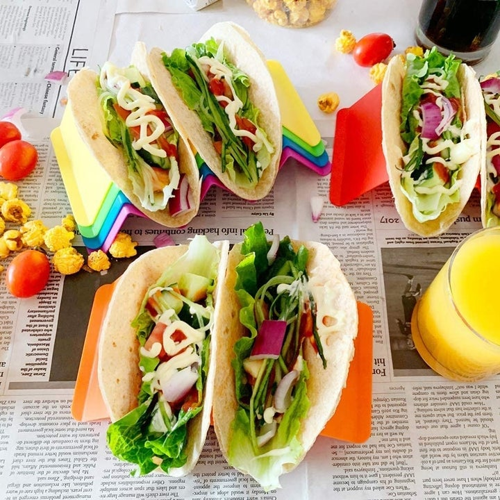 Red, orange, and yellow taco holders carrying soft shell tacos with all the fixings