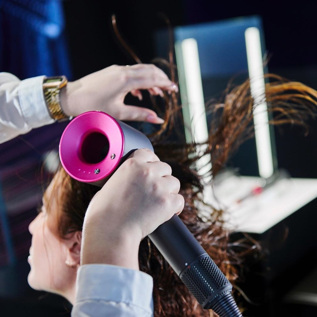 A stylist uses the hairdryer on a client