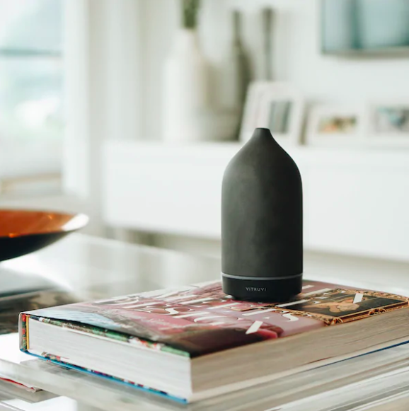 The stone diffuser perched on a stack of coffee table books