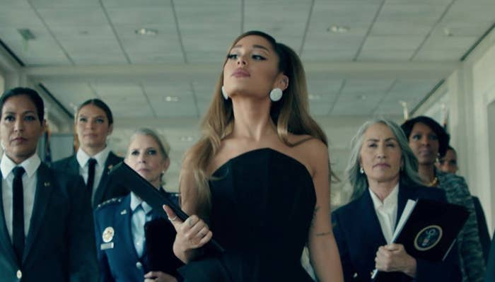 """Ariana Grande walks in front of group of sharply dressed women in her music video """"Positions."""""""