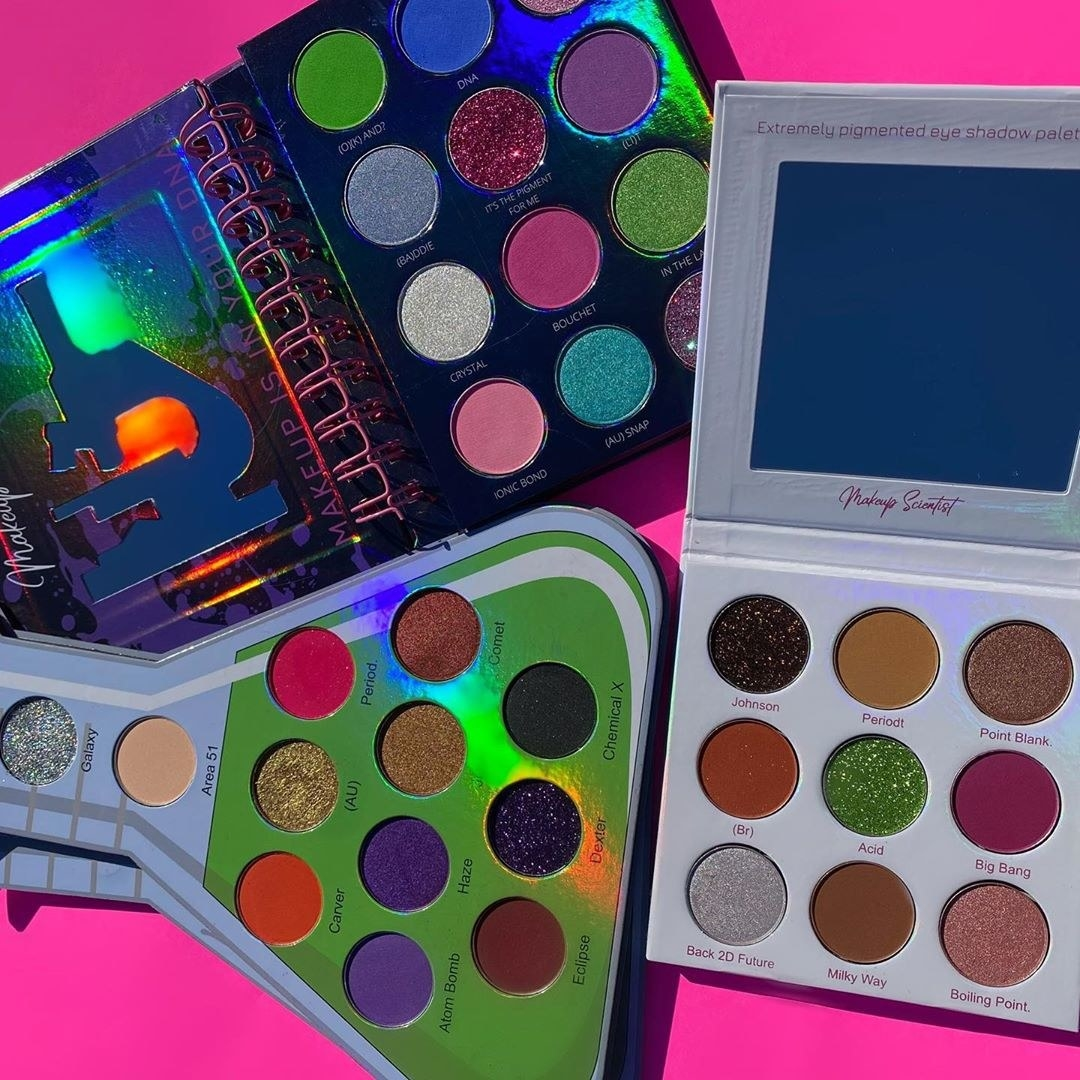 Three eyeshadow palettes in science-related themes, like a lab manual and beaker