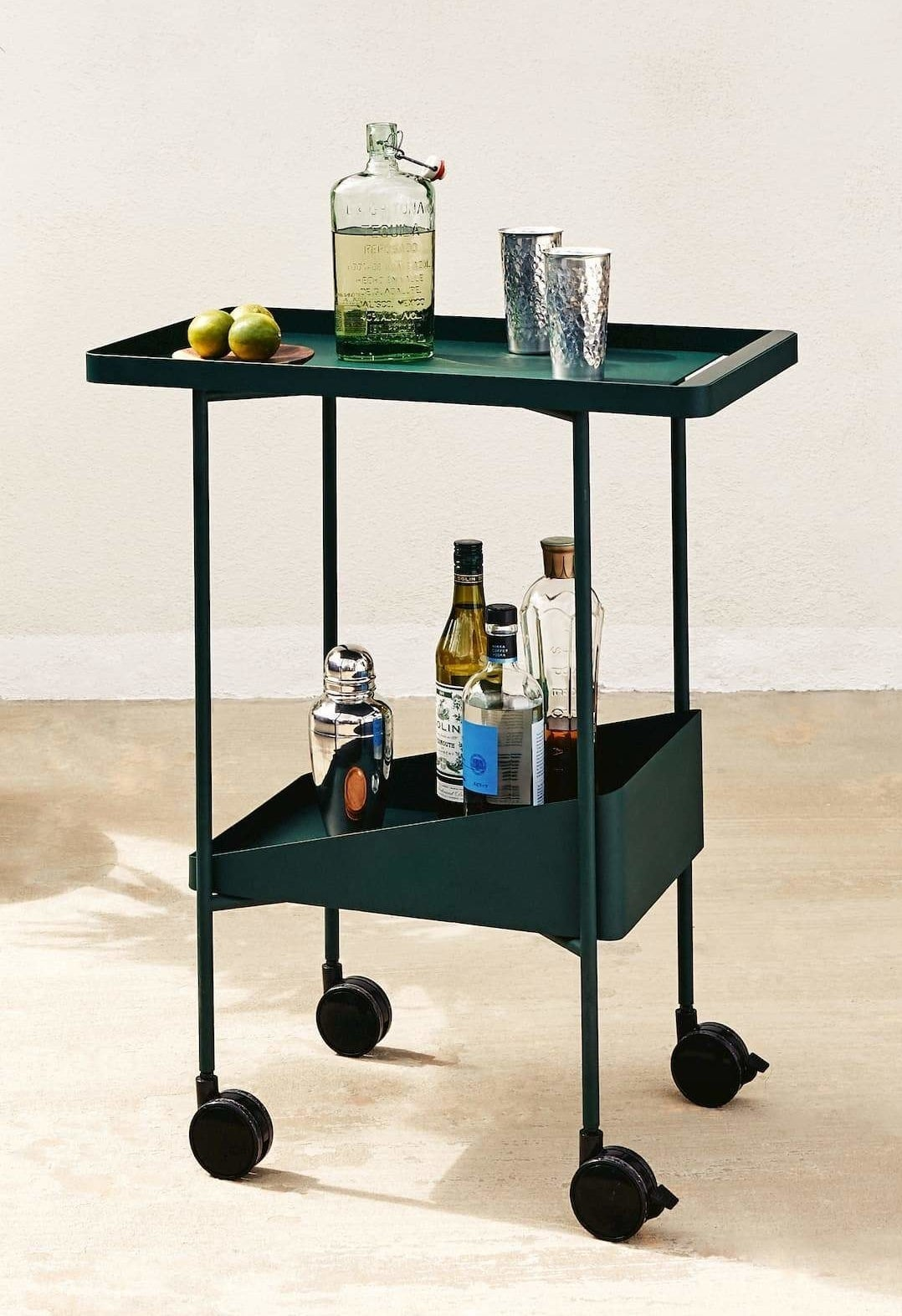 A dark green rolling trolley cart with a serving top and bottom shelf filled with bottles and cocktail supplies