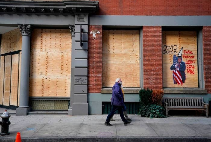 A couple walking past boarded up shop windows with anti-Trump graffiti on them