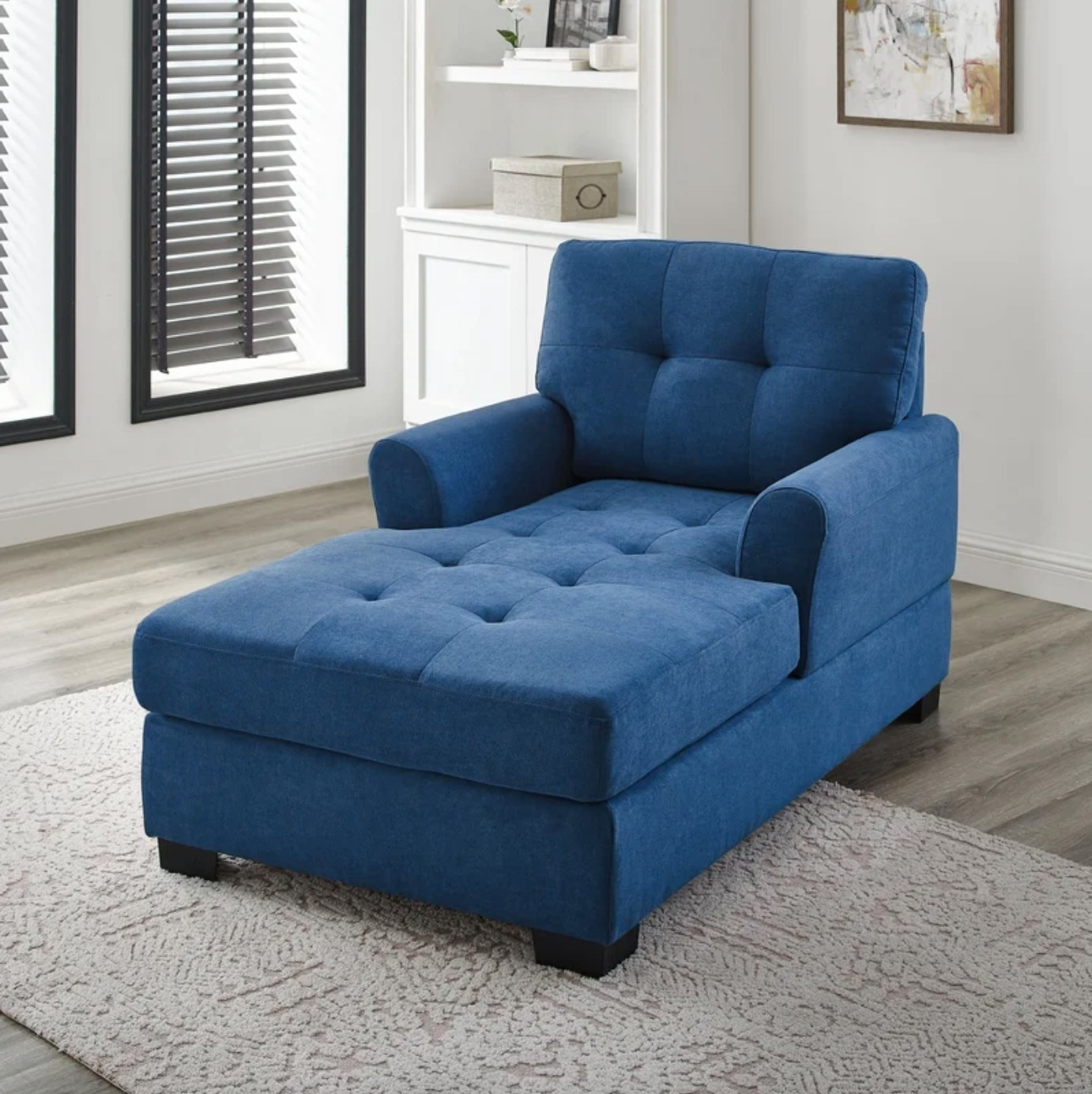 The chaise lounge in blue in a neutral-colored room