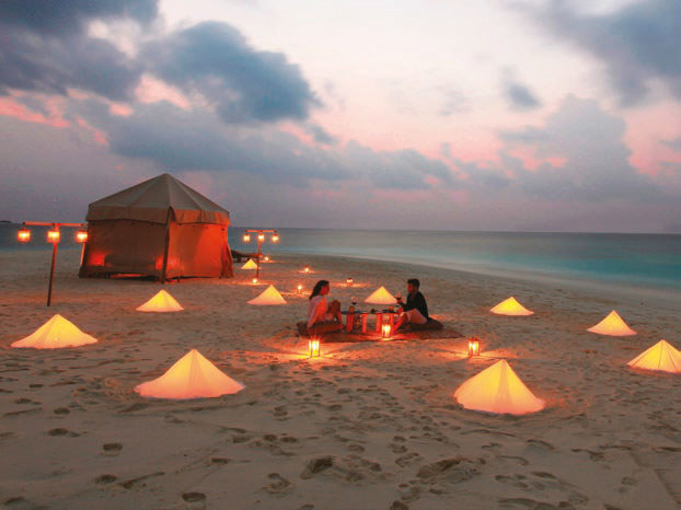 A couple sitting on a deserted beach next to a luxury tent surrounded by lanterns