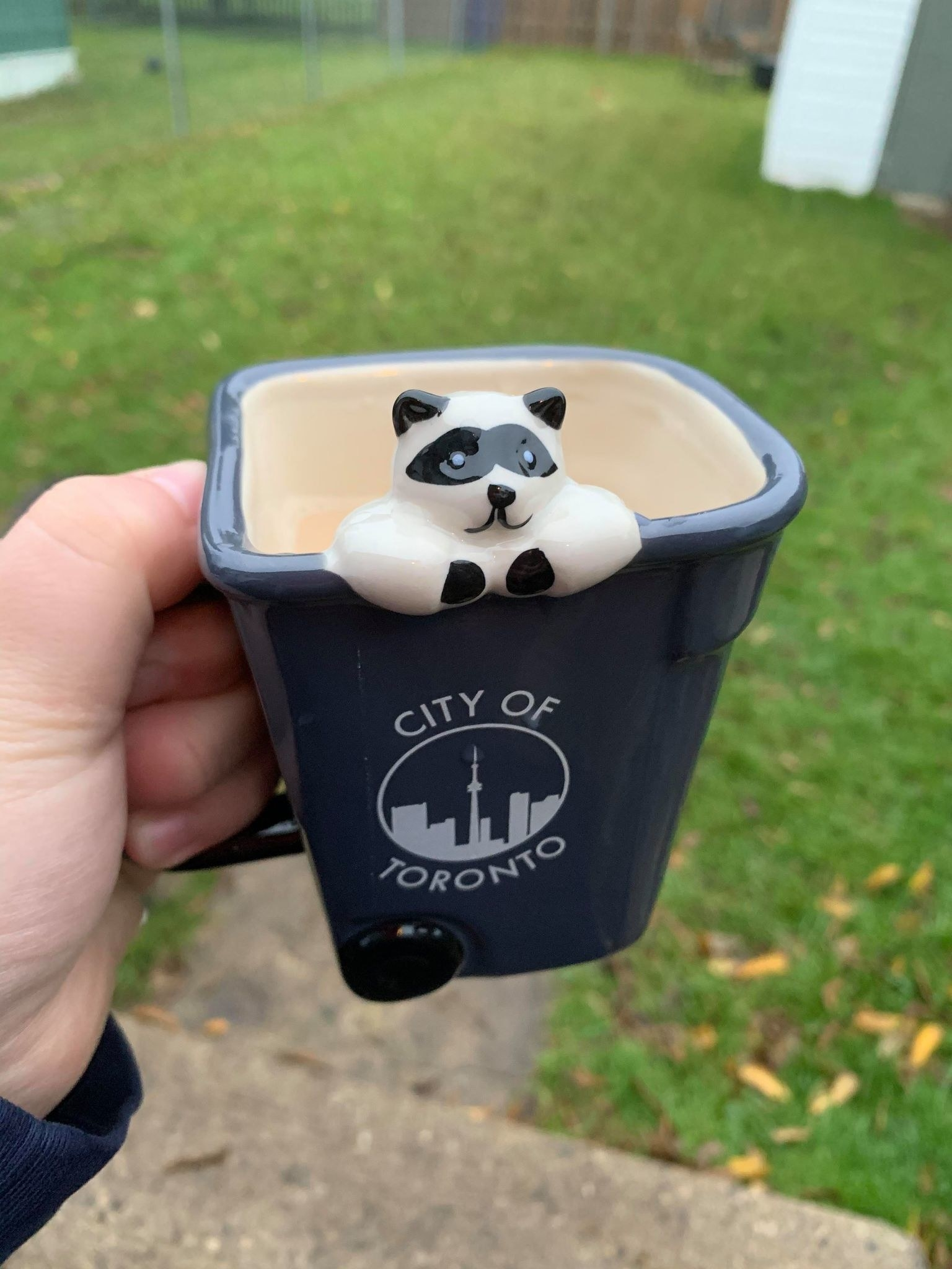 A hand holding a mug shaped like a Toronto garbage bin with a raccoon poking out