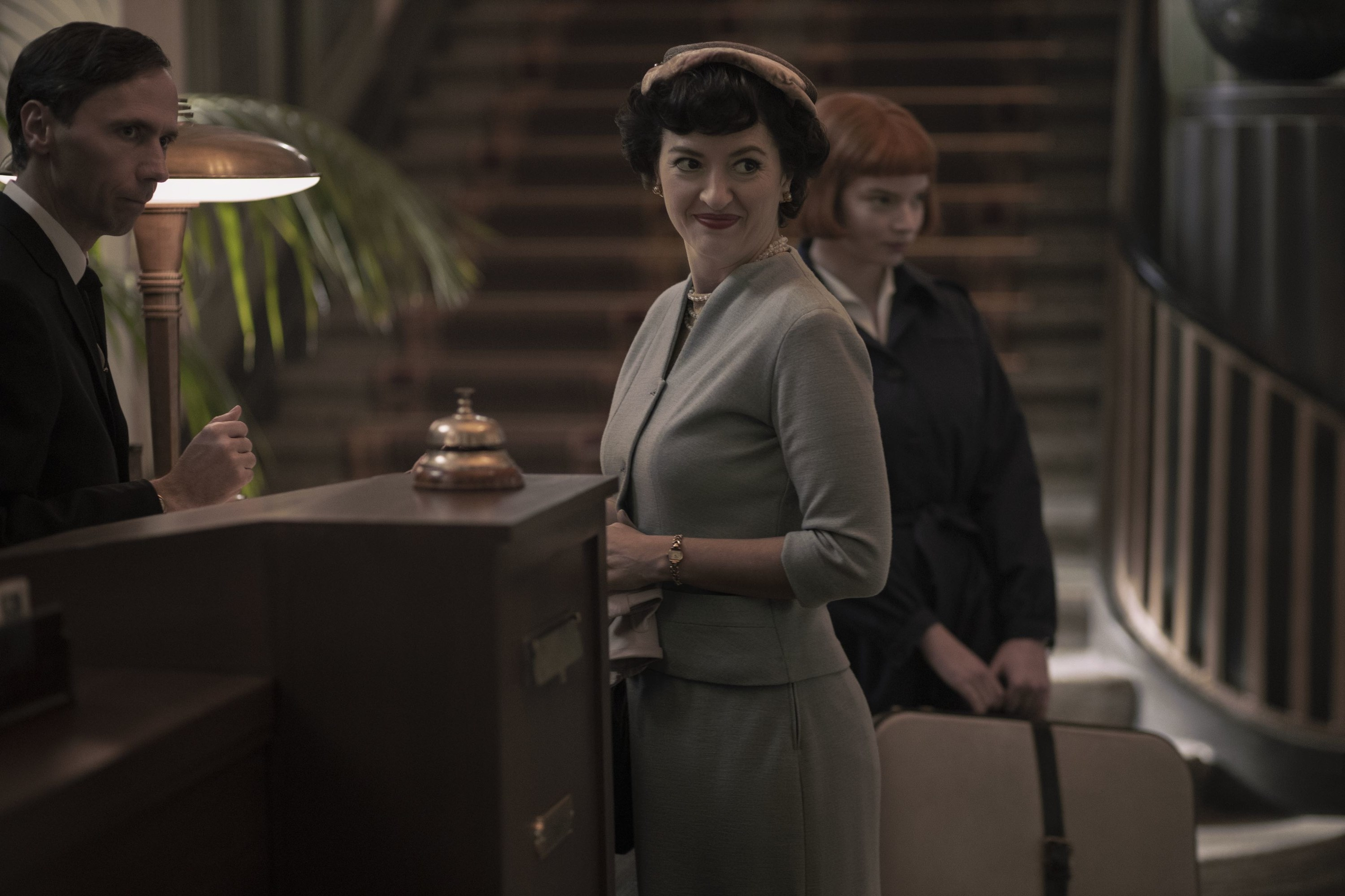 Alma standing in front of a hotel concierge with Beth standing behind her holding a suitcase