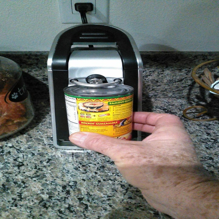 Reviewer places can of refried beans under black electric can opener