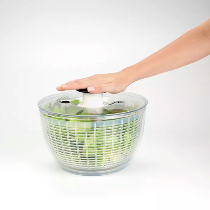 Hand pushes down on clear salad spinner to spin lettuce inside