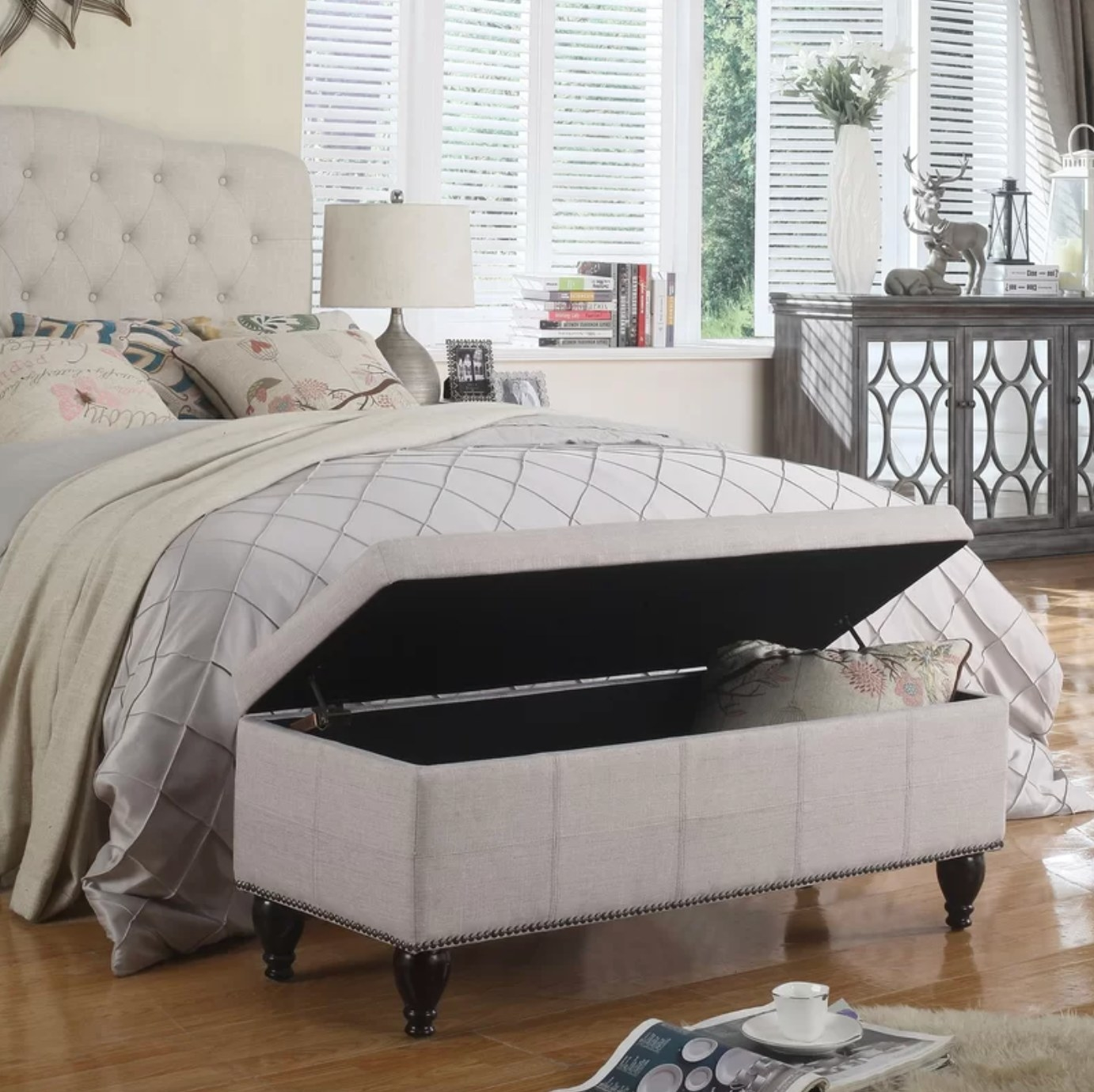 The upholstered storage bench in beige at the foot of a bed