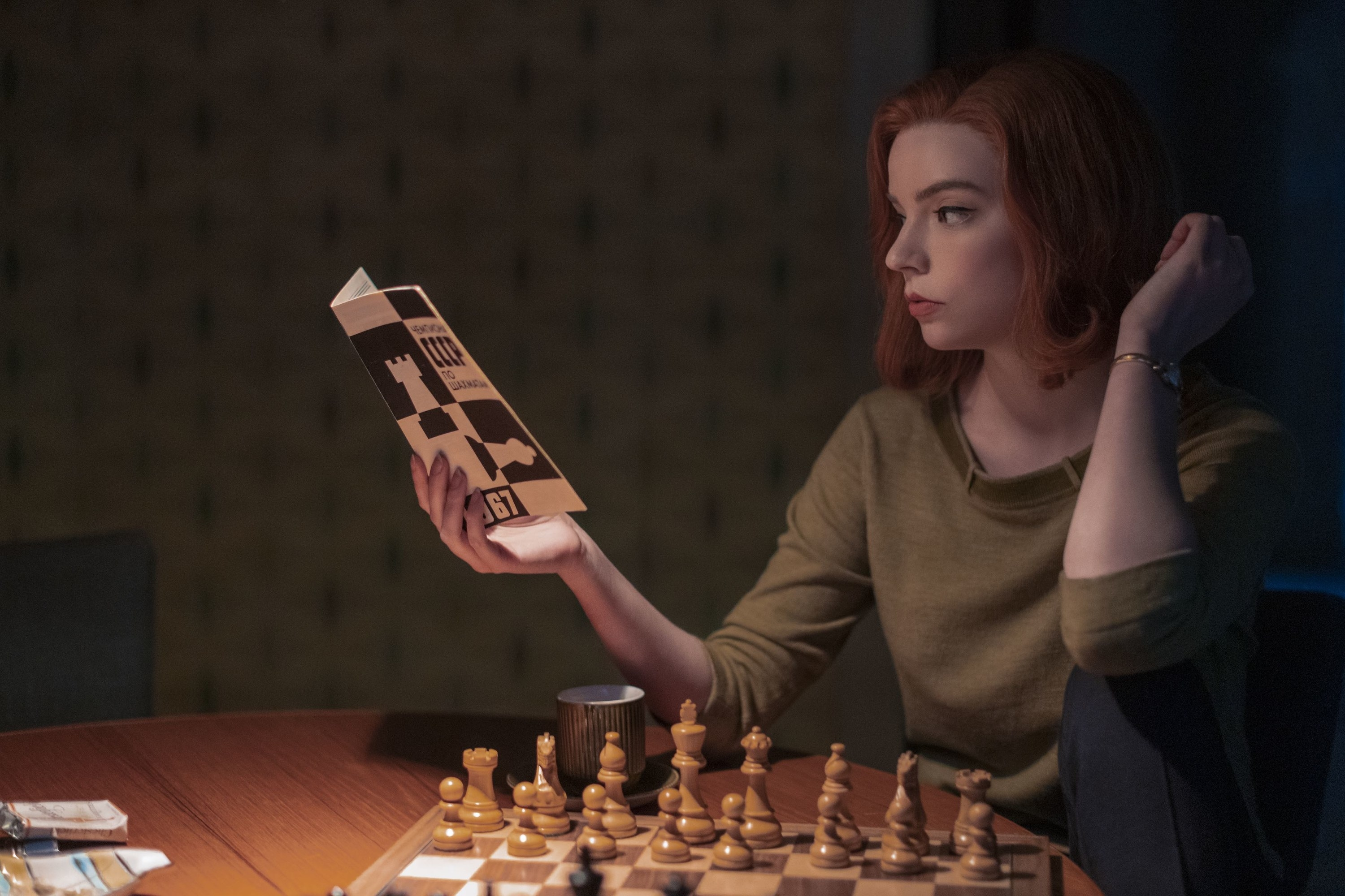 Beth reading a book while sitting in front of a chess set