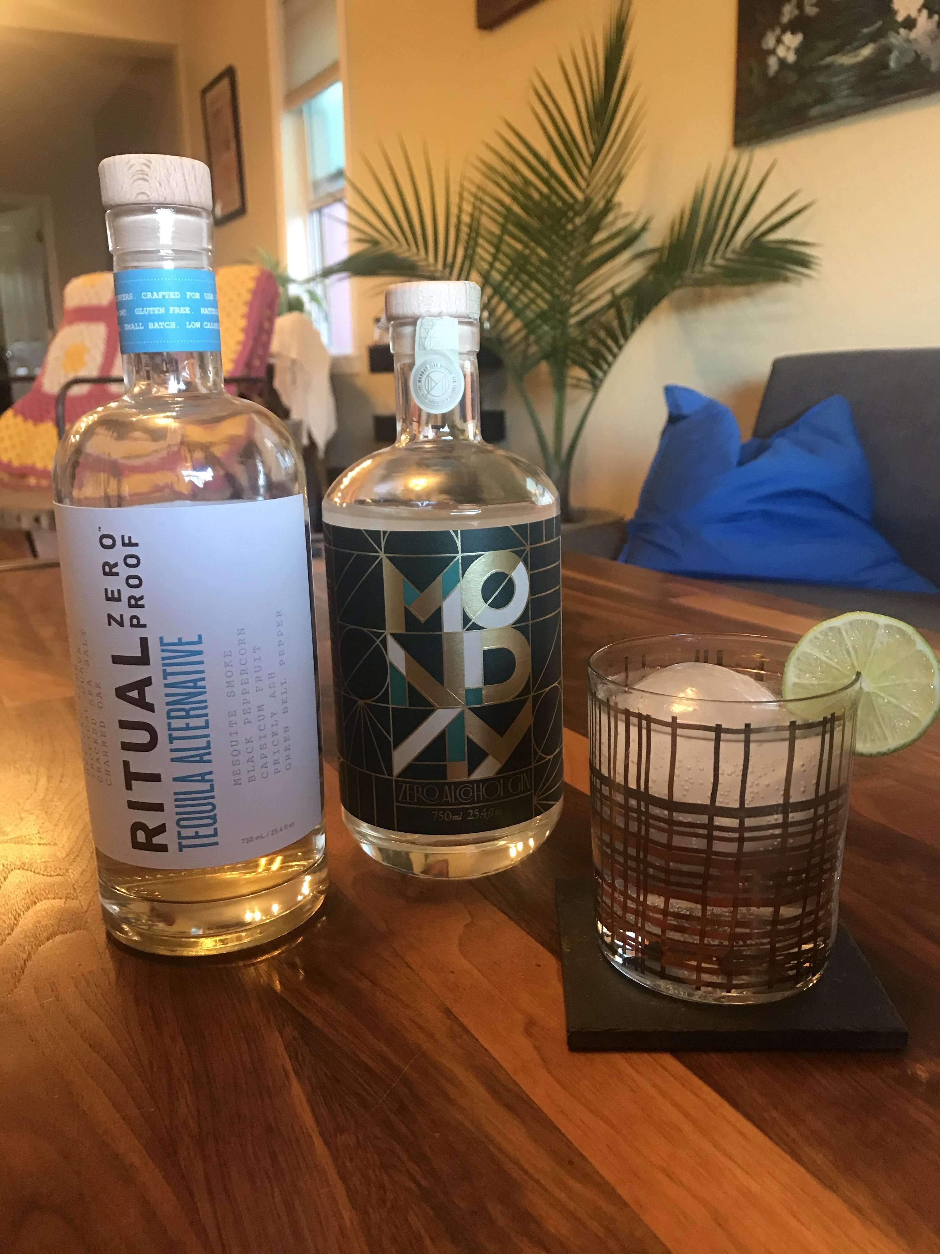The gin and tequila alternatives in their bottles next to a glass