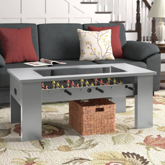 The foosball table in gray being used as a coffee table