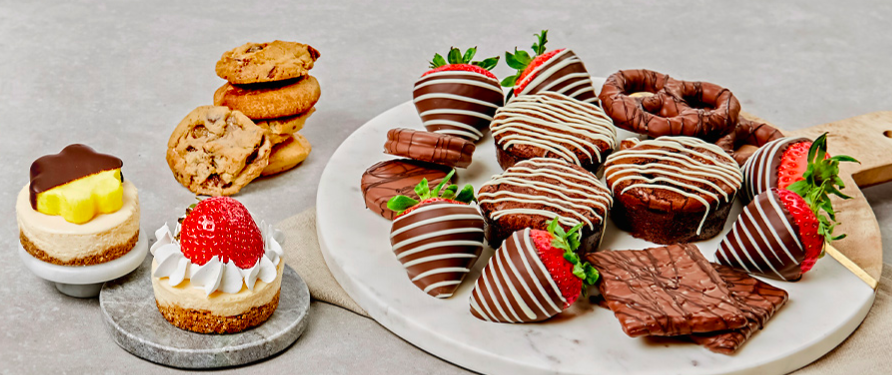 A platter full of baked goods and chocolate covered fruits
