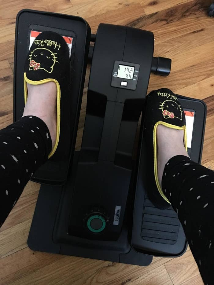 Reviewer pedals feet on black desk elliptical while wearing Hello Kitty slippers