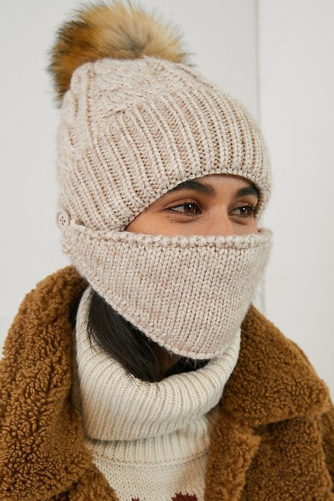 A model wearing the face mask and hat in ivory