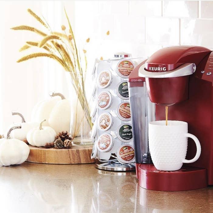 A red Keurig K-classic pouring coffee into a mug