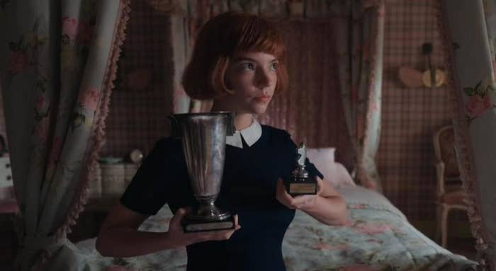 Beth Harmon holding up her chess trophies.