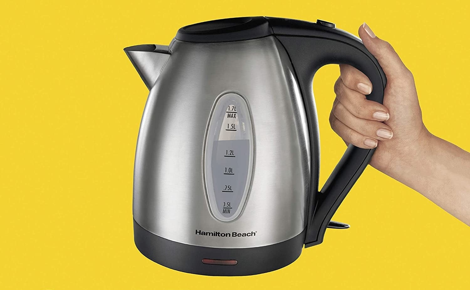 hand holds large kettle with window to show liquid inside and measurements