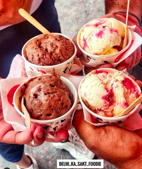 Several people holding cups of ice-cream