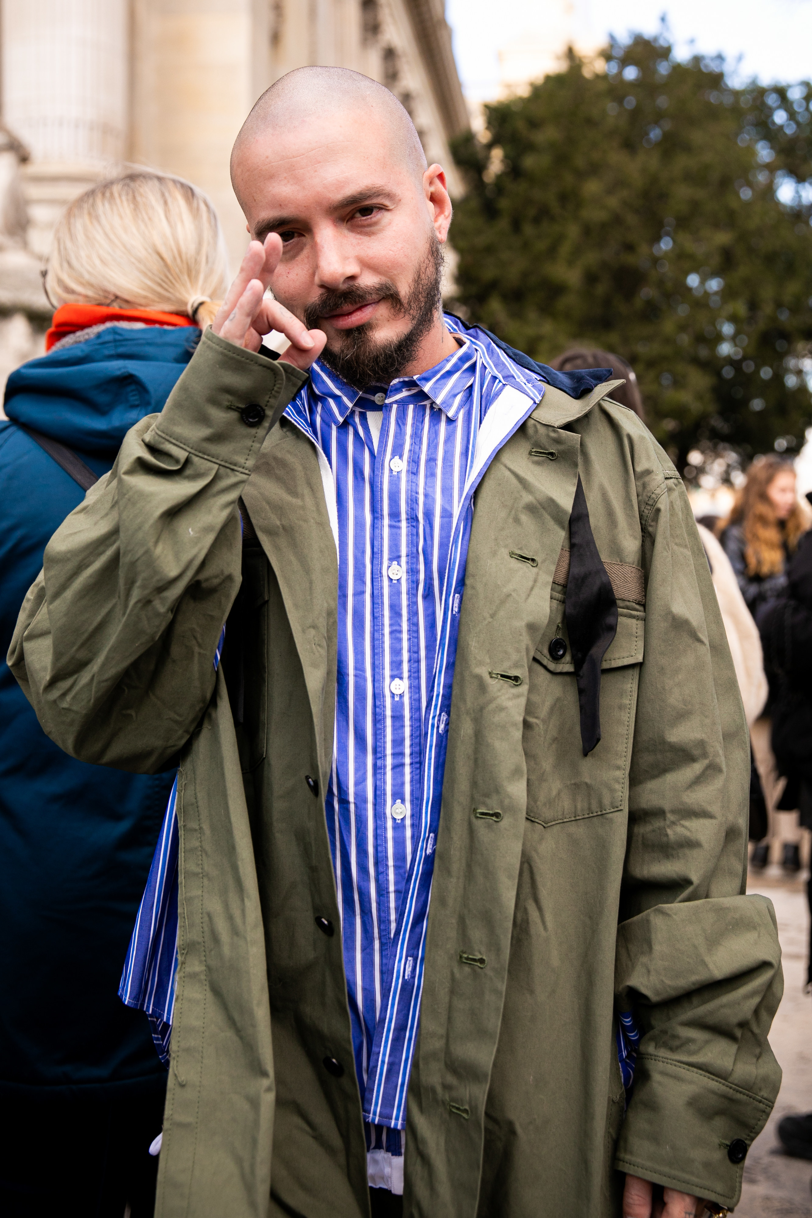 J Balvin, wearing a blue striped shirt and khaki jacket, is seen outside the Sacai show during the Paris Fashion Week - Menswear F/W 2020-2021 on on January 18, 2020 in Paris, France