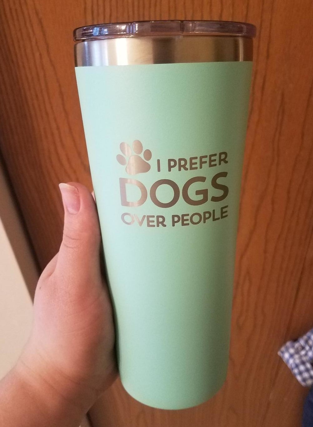 """Reviewer holding mint green tumbler that has the words """"I prefer dogs over people"""" on it"""