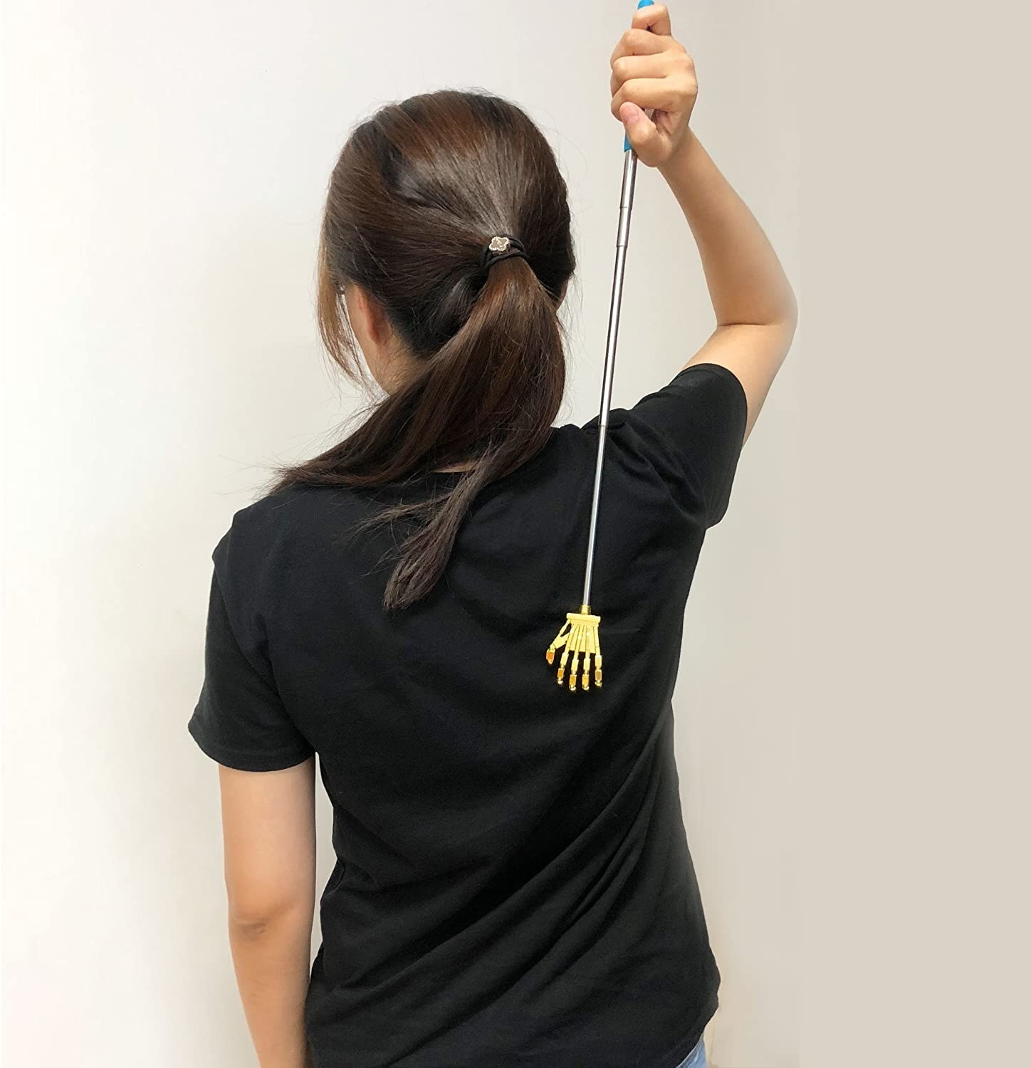 A person using the back scratcher while wearing a tee