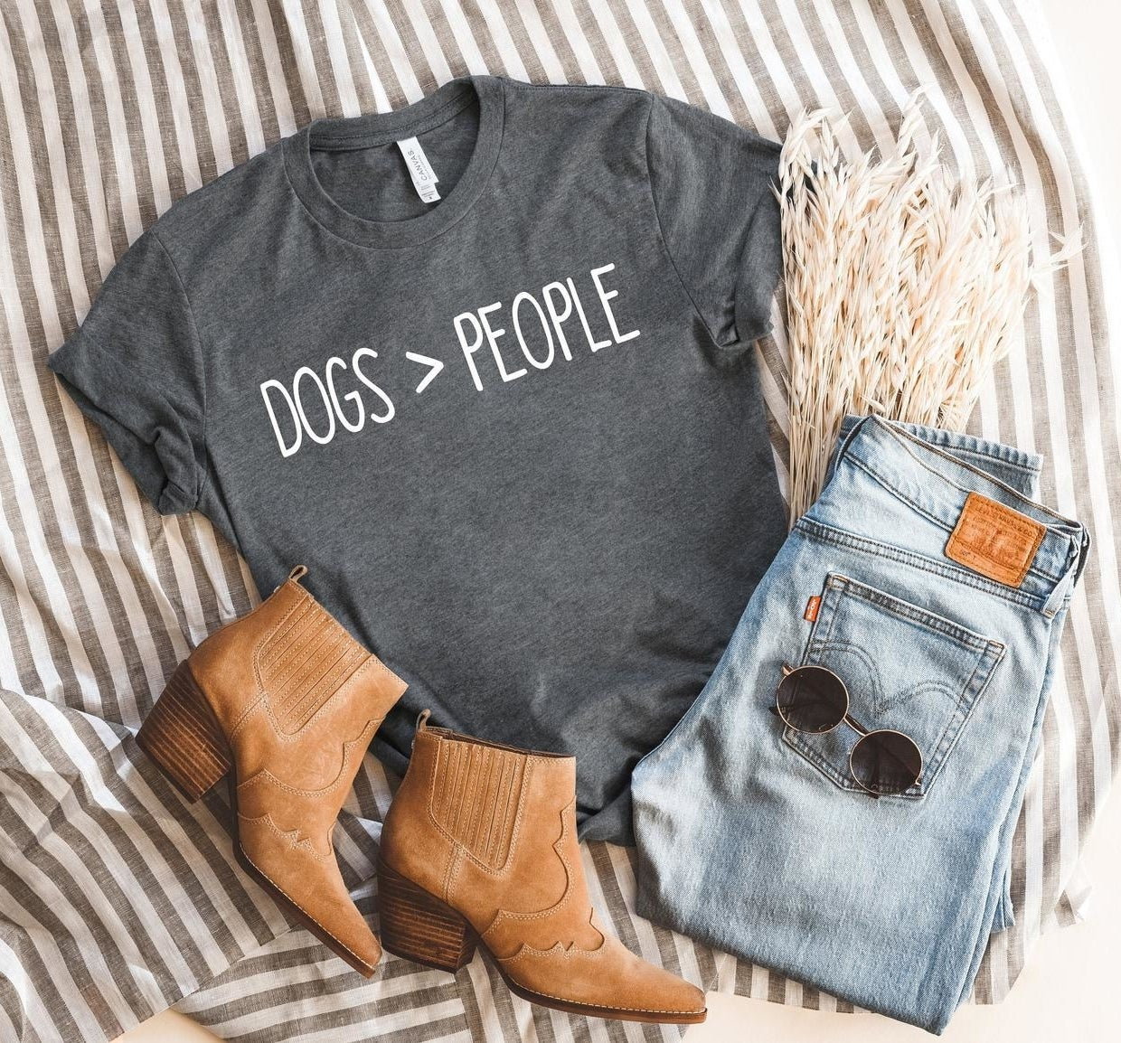 """Flatlay shot of the T-shirt that says """"Dogs > people"""" with a complete outfit of boots and jeans"""