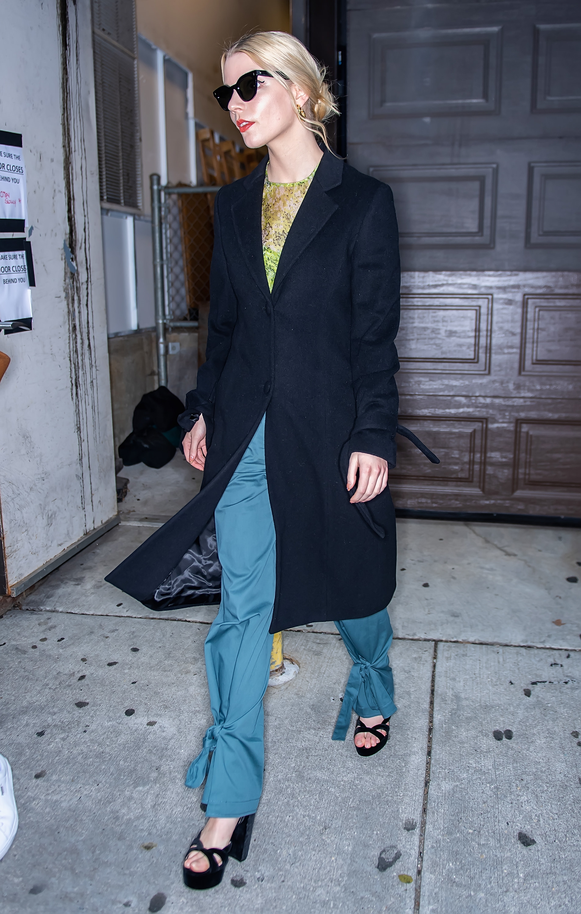 Anya Taylor-Joy walking in a long coat, sunglasses, and platform heels