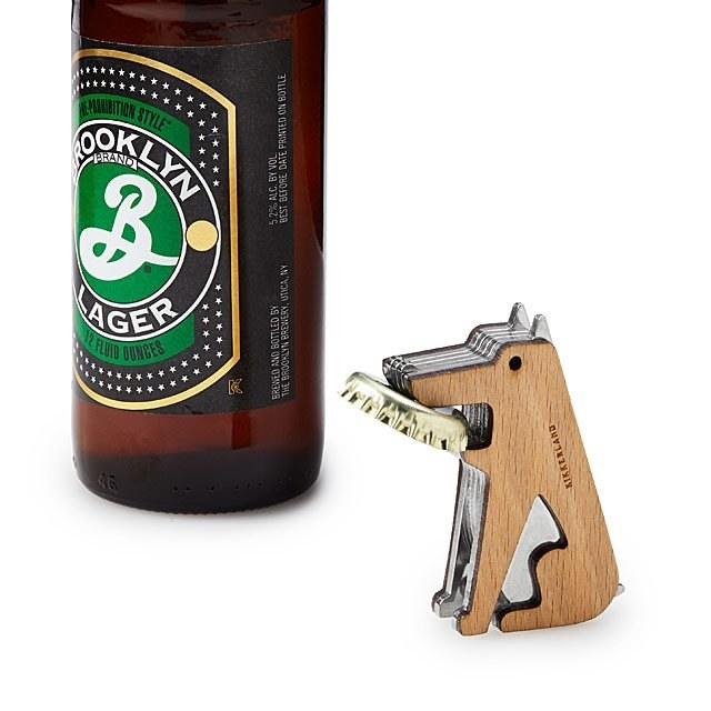 A beer beside the dog bottle opener with a bottle cap in its mouth