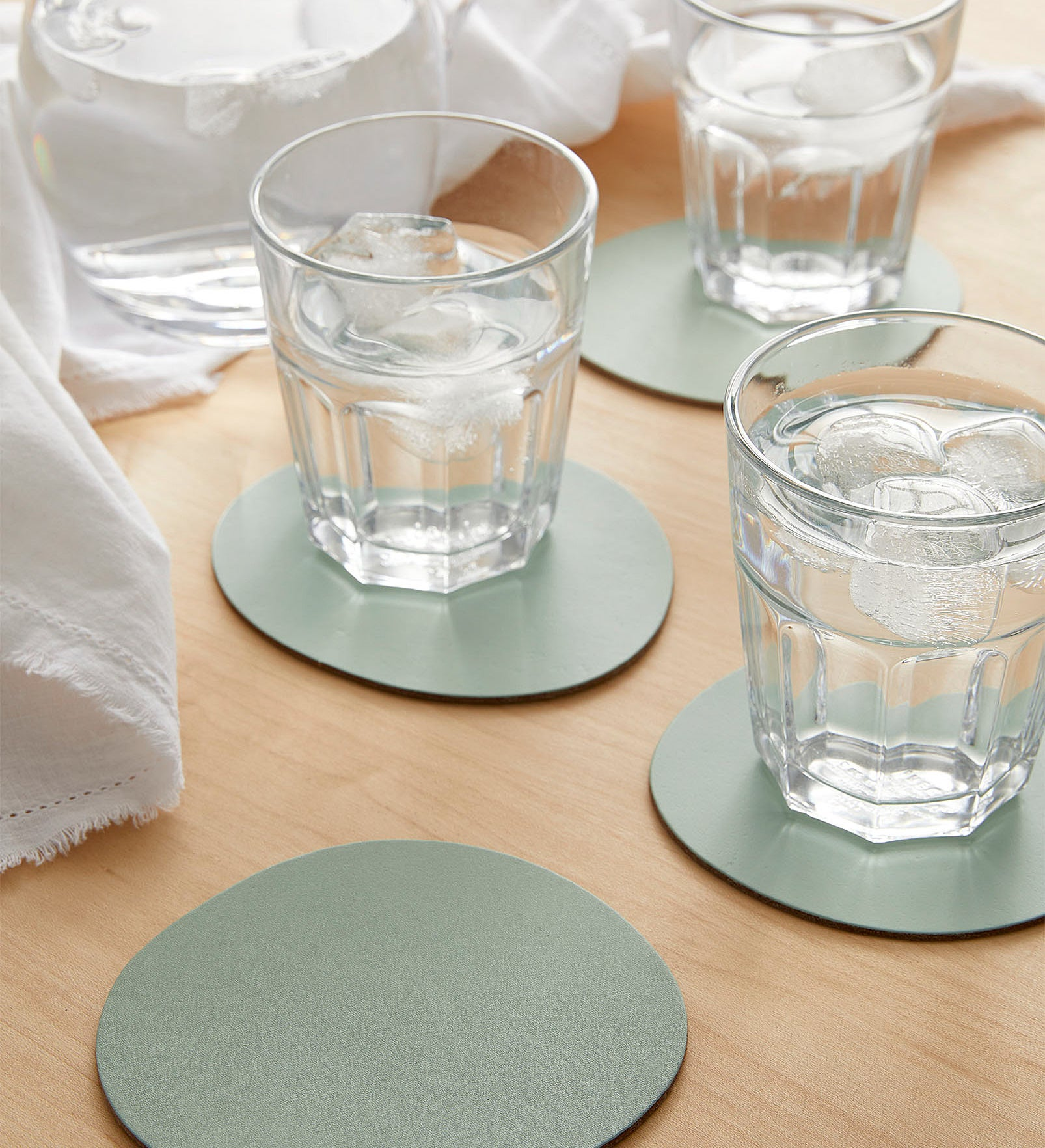 The coasters with glasses of water on them