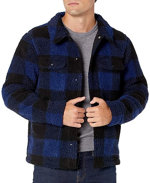 Model wearing the sherpa jacket in black and blue plaid with pockets on either side of the chest