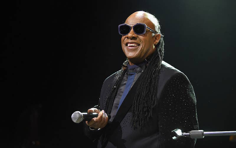 Stevie Wonder performing onstage, holding a microphone and wearing sunglasses
