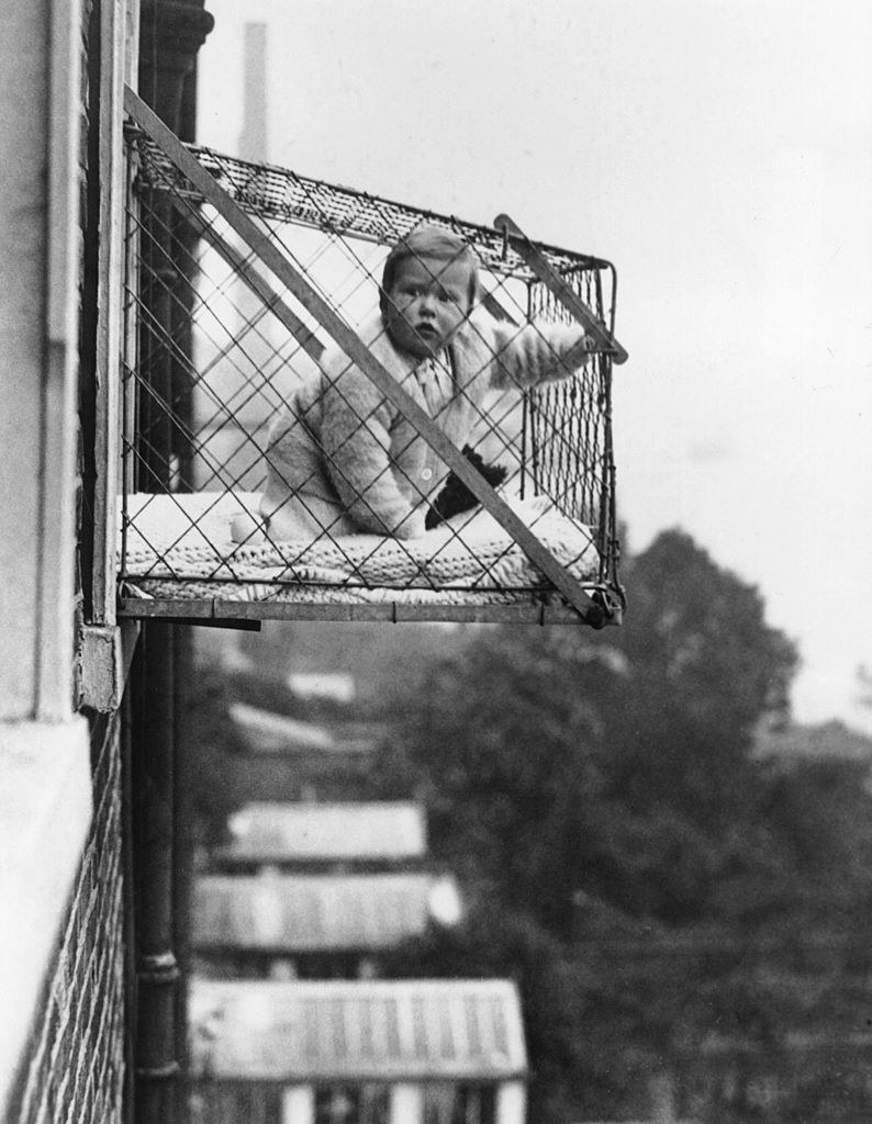 A baby sitting in a cage strapped to the outside of an apartment building window several stories up