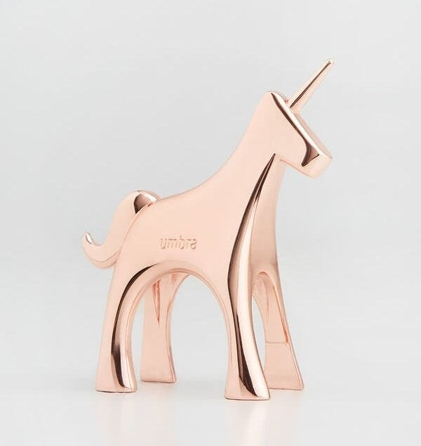 A rose gold unicorn statuette with a horn for stacking rings