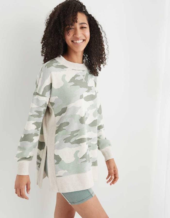 Model in green and cream camo sweatshirt