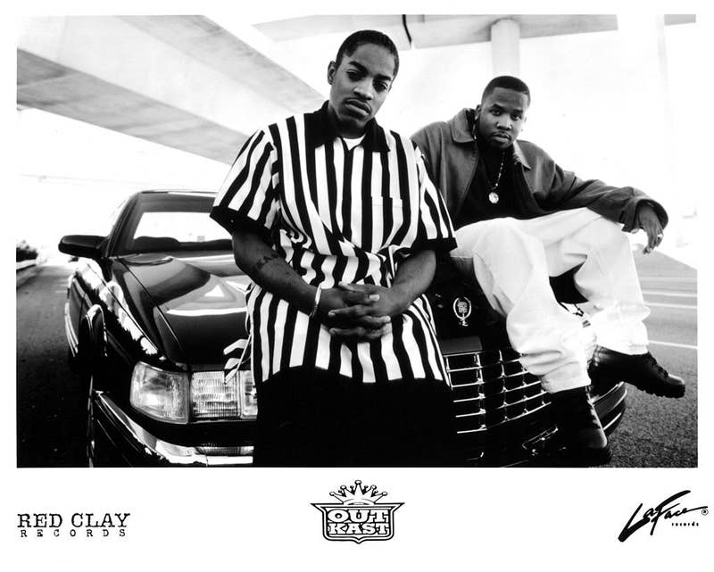 Outkast posing on top of a car in a black and white image in the early '90s