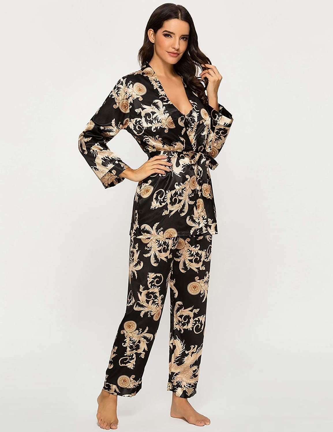 Model wearing the pajamas in black with gold floral pattern on them