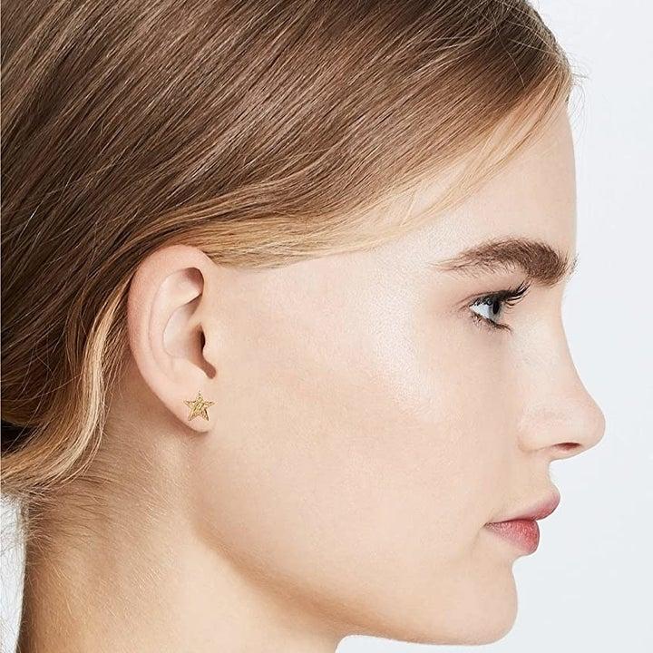 model wearing the gold star earrings
