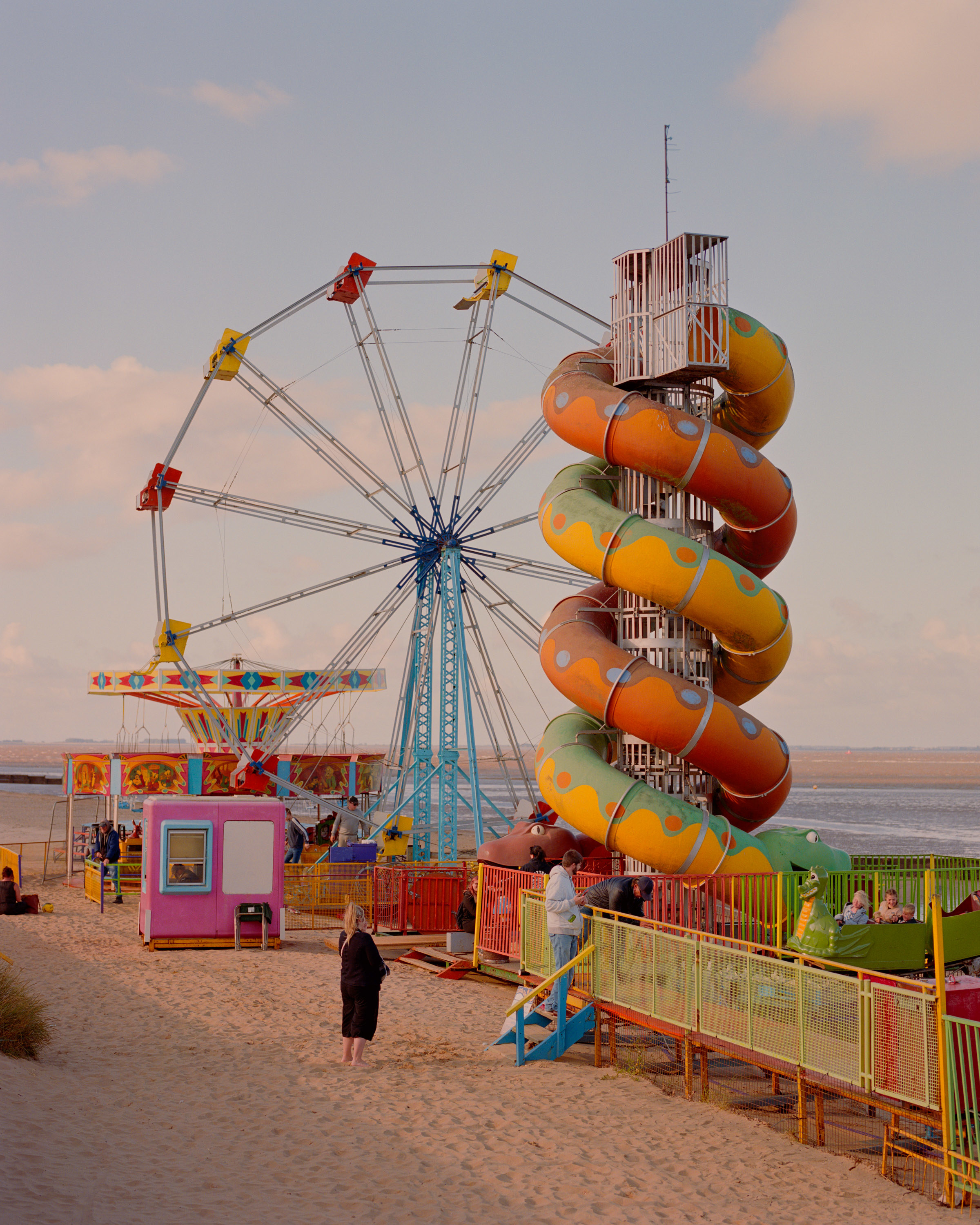 A woman in black and a man in a white sweatshirt stand next to colorful carnival equipment on the beach.