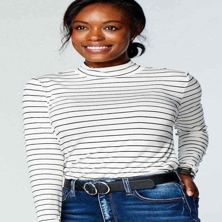 Model wearing black and white stripe mock turtleneck top