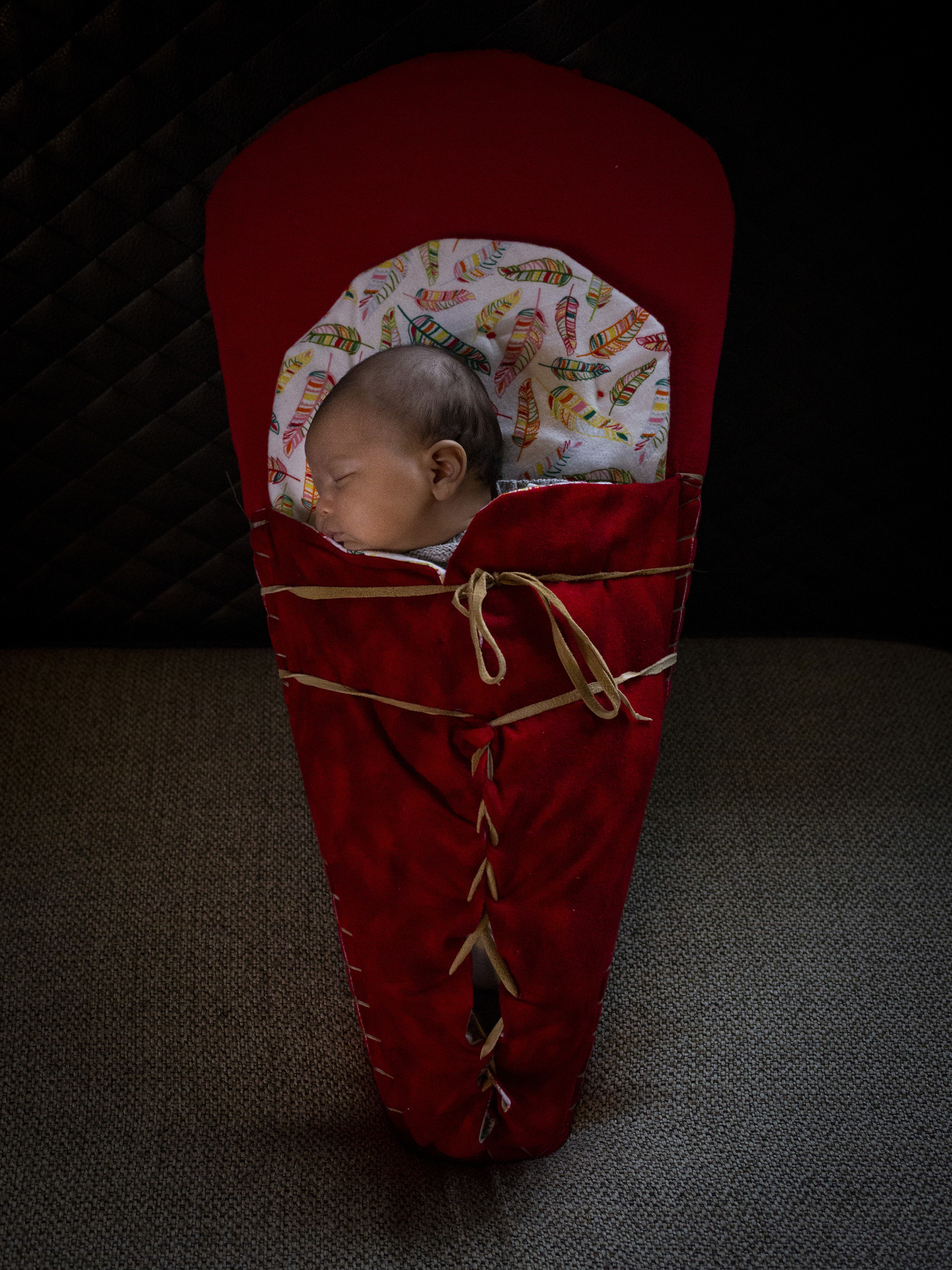 A baby sleeping wrapped in red.