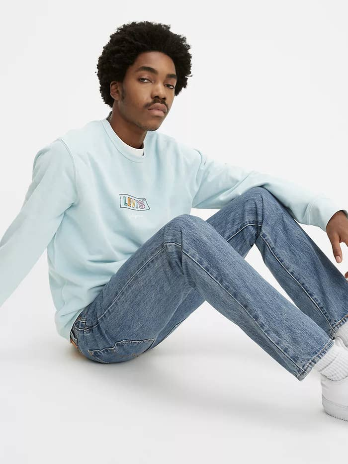 model sits on the floor wearing straight leg jeans