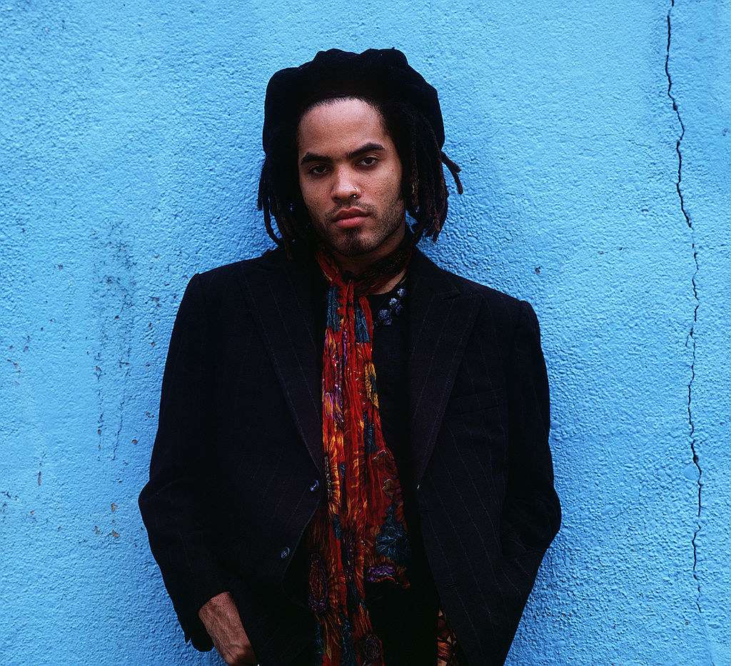 Lenny Kravitz posing in front of a blue wall in 1989 while wearing a hat and colorful scarf