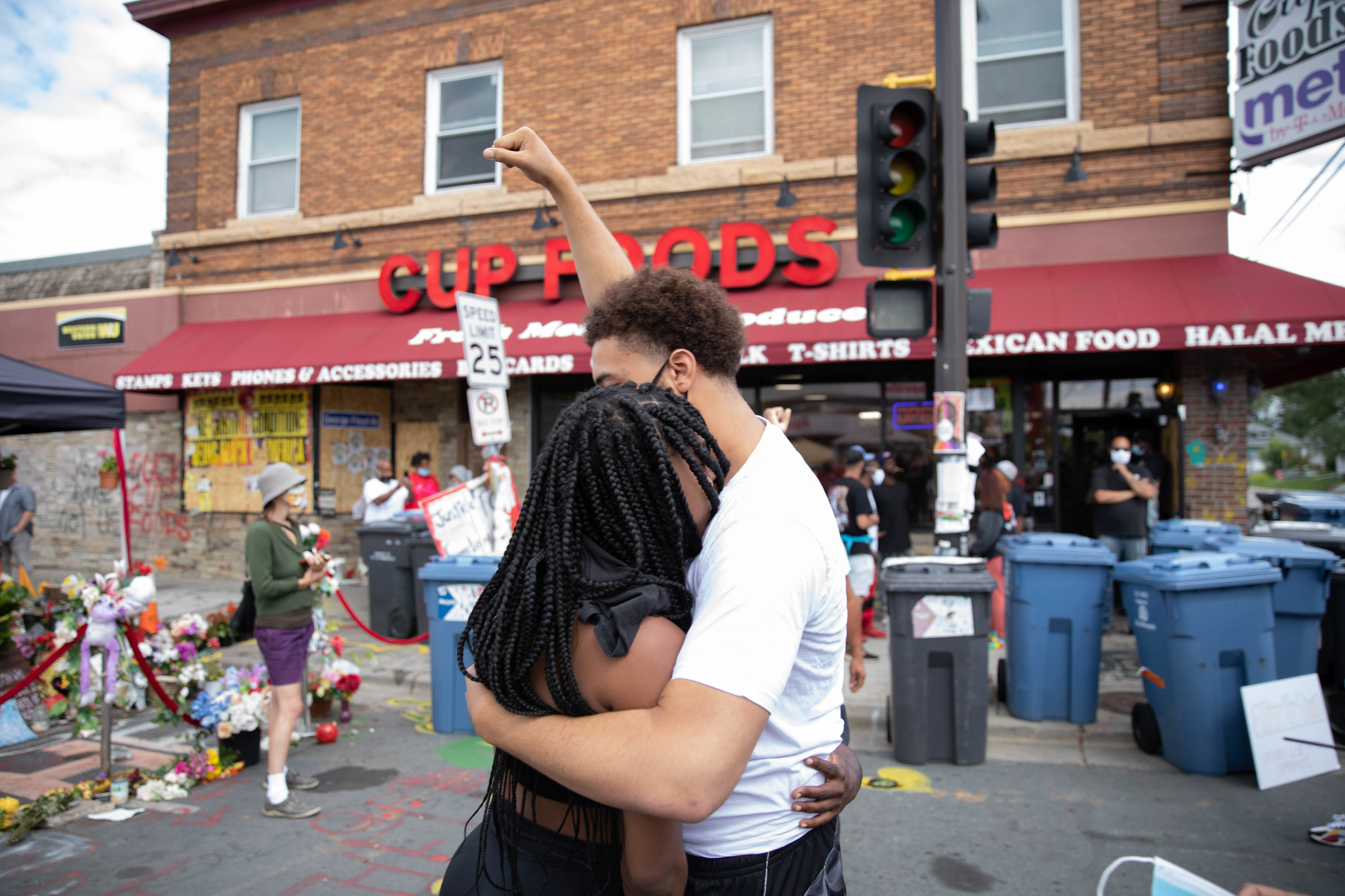 A woman with braids hugs a man raising his fist in front of a grocery store, stoplights, and blue recycling bins.