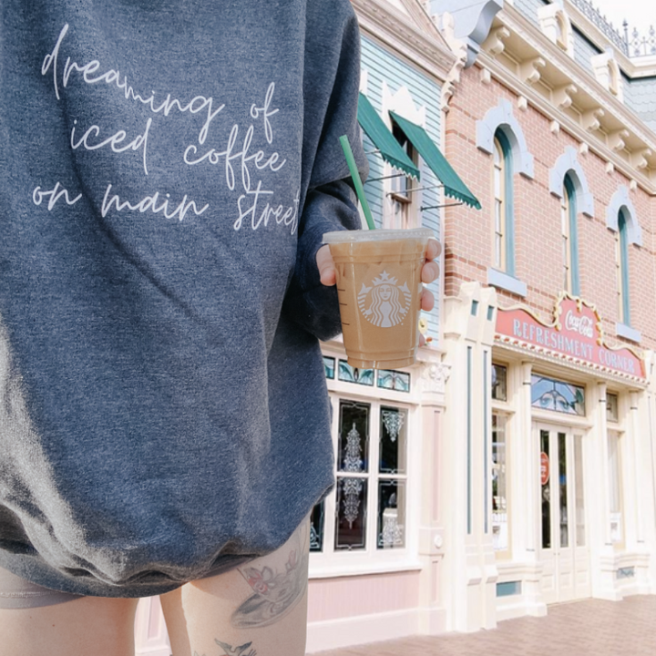 "a model wearing the sweatshirt in gray with script writing that says ""dreaming of iced coffee on main street"""